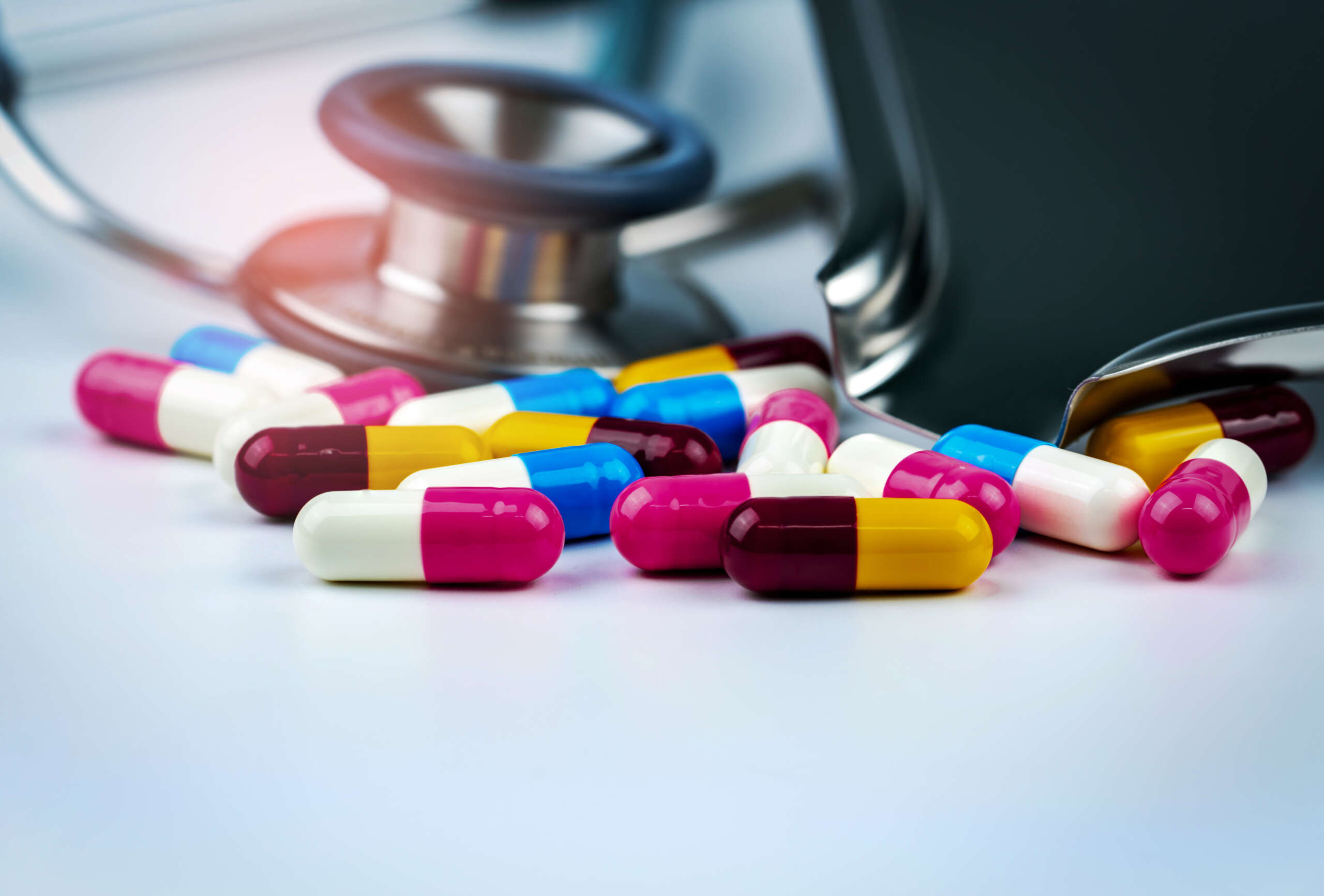 Stethoscope with pile of colorful antibiotic capsule pills on white table with drug tray. Antimicrobial drug resistance and overuse. Medical equipment for doctor. Global healthcare. Pharmaceuticals.